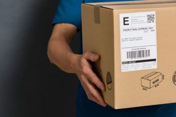 Closeup hands of delivery man holding package to deliver. Courier hand holding brown box isolated on grey background. Detail of delivery man carrying cardboard parcel with label with copy space.